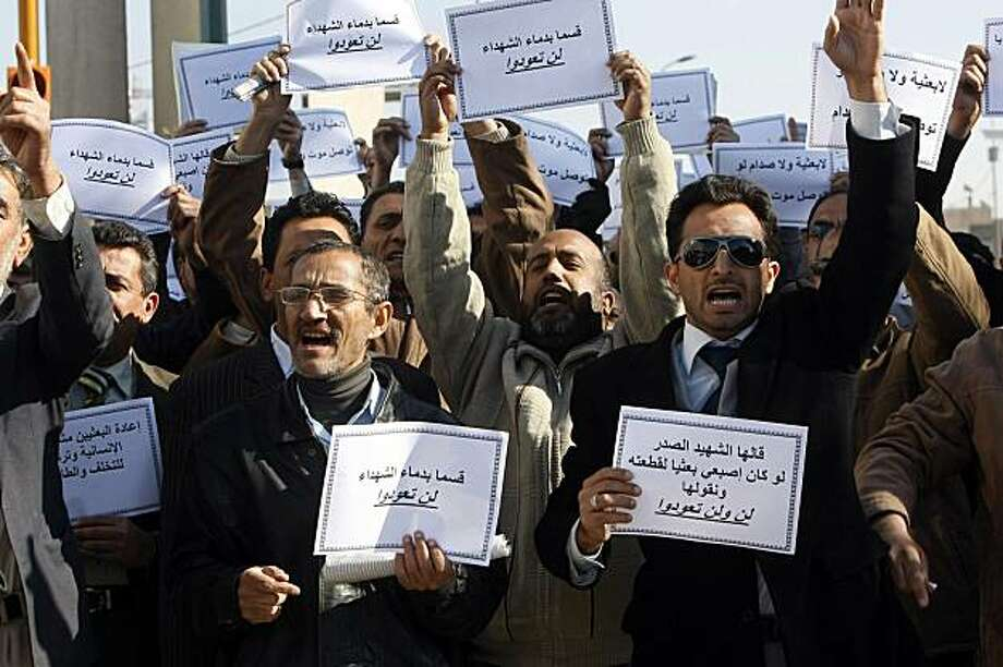 "Iraqi men shout slogans and hold signs that read in Arabic ""We swear by the blood of martyrs, you will not return"" during a protest in Baghdad on February 7, 2010 against the stand in the upcoming elections of some candidates with links to the outlawed Baath party. The Iraqi electoral commission announced on February 3 that a panel of seven judges had ruled that 500 candidates barred from running in next month's general elections because of alleged links to the outlawed Baath party of executed dictator Saddam Hussein -- can stand in the March 7 polls. The judges decided to reinstate the barred candidates, saying they would examine their files after the polls and would eliminate them if they were found to be Baathists. Photo: Sabah Arar, AFP/Getty Images"