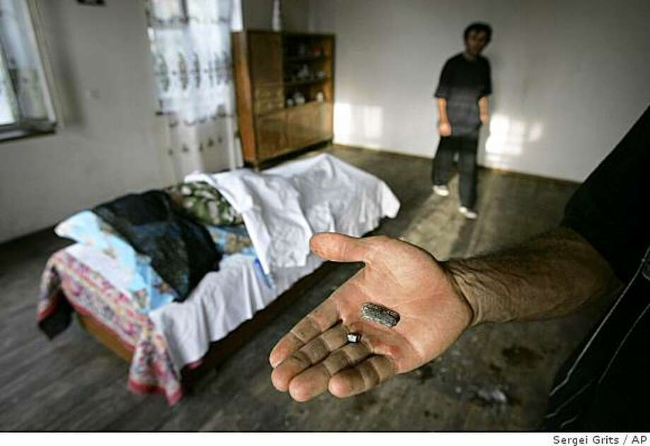 A man holds pieces of shrapnel, which relatives claim killed Natela Guraspashvili, seen in background at left, in the village of Ruisi, near the Georgian breakaway province of South Ossetia,  Tuesday, Aug. 12, 2008. Three villagers were killed and five wounded after a Russian air raid Tuesday morning, residents said. (AP Photo/Sergei Grits) Photo: Sergei Grits, AP