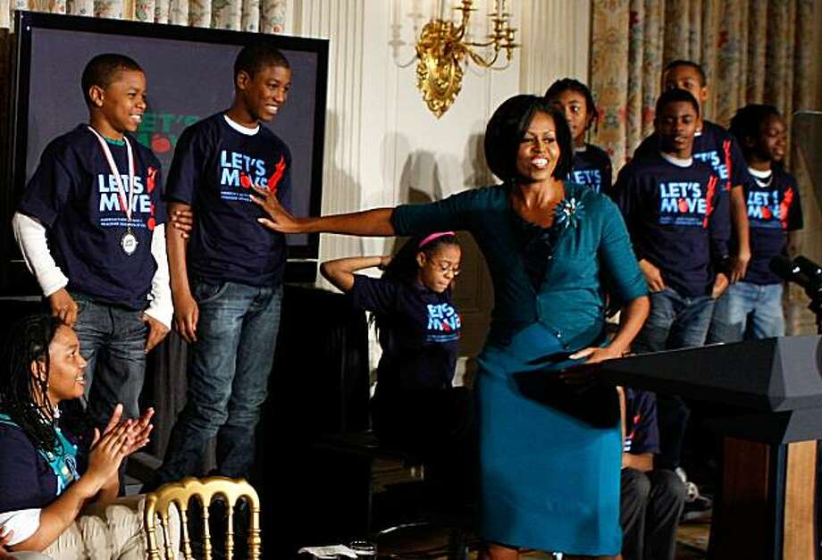 "WASHINGTON - FEBRUARY 09:  U.S. first lady Michelle Obama introduces members of the 2009 national championship pee-wee football team, Watkins Hornets, during an event to promote fighting childhood obesity at the State Dining Room of the White House February 9, 2010 in Washington, DC. The first lady announced the ""Let's Move"" campaign with the goal to combat the epidemic of childhood obesity within a generation. Photo: Alex Wong, Getty Images"