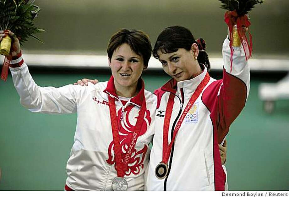 Silver medallist  Natalia Paderina (L) of Russia and bronze medallist Nino Salukvadze of Georgia pose after the women's 10m air pistol shooting competition at the Beijing 2008 Olympic Games August 10, 2008. Photo: Desmond Boylan, Reuters