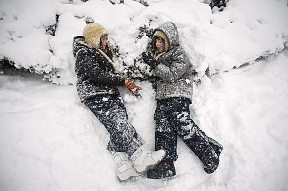 Olivia Wilkins, 10, and Clare Carty, 9, from left, of Hoboken lie in the snow as they enjoy the day in Elysian Park as heavy snow falls  Wednesday. Photo: Joe Epstein, AP