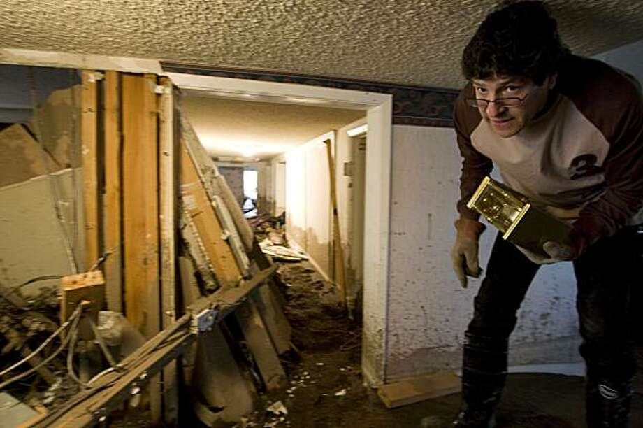 Henry Laguna recovers some personal belongings after a mudslide caused by heavy rains damaged his house in La Canada Flintridge, Calif., a neighborhood of Los Angeles, on Monday. Photo: Hector Mata, AP