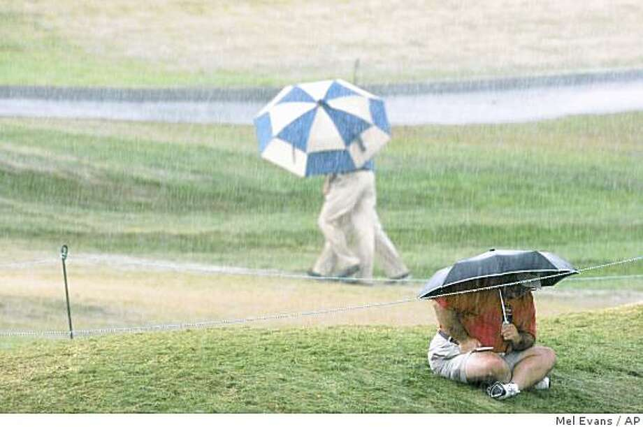 People evacuate the course, as one spectator remains under his umbrella, as the severe thunderstorm blows through the area during the third round of the 90th PGA Championship golf tournament Saturday, Aug. 9, 2008, at Oakland Hills Country Club in Bloomfield Township, Mich. (AP Photo/Mel Evans) Photo: Mel Evans, AP
