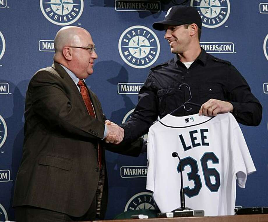 Seattle Mariners general manager Jack Zdurienick, left, shakes hands with pitcher Cliff Lee, right, during a baseball news conference at Safeco Field in Seattle on Friday, Jan. 22, 2010. Lee was acquired by the Mariners in a trade with the Philadelphia Phillies last December. Photo: John Froschauer, AP