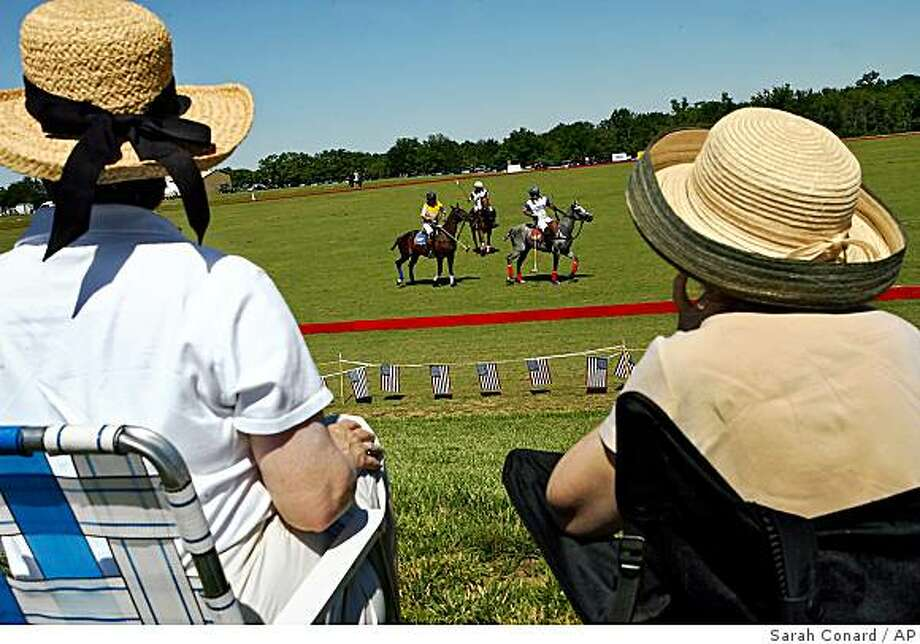 **APN ADVANCE FOR SUNDAY AUG. 10 ** Spectators watch a charity polo match at Blue Heron Polo Club on Sunday, June 15, 2008, in Defiance, Mo. The St. Louis Polo Club has launched new offerings to bring polo to the masses where on Sunday afternoons, for $10 a carload, spectators can come out to Blue Heron Polo Club and watch a match and beginners who want to learn how to play polo can also take lessons at a nearby property, on borrowed horses, for $75 a class. (AP Photo/ Sarah Conard) Photo: Sarah Conard, AP