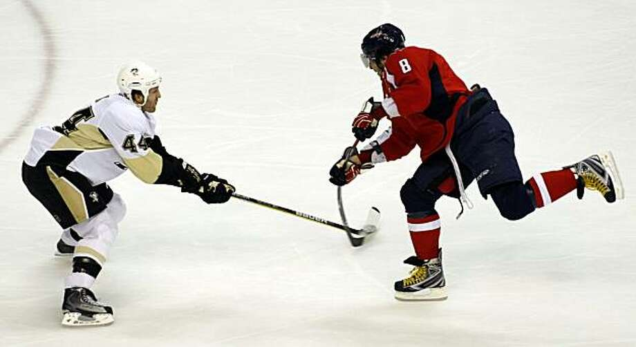 Washington Capitals' Alex Ovechkin (8), of Russia, shoots the puck past Pittsburgh Penguins' Brooks Orpik, left, during the first period of an NHL hockey game Sunday, Feb. 7, 2010, in Washington. The Capitals won 5-4 in overtime. Photo: Luis Alvarez, AP