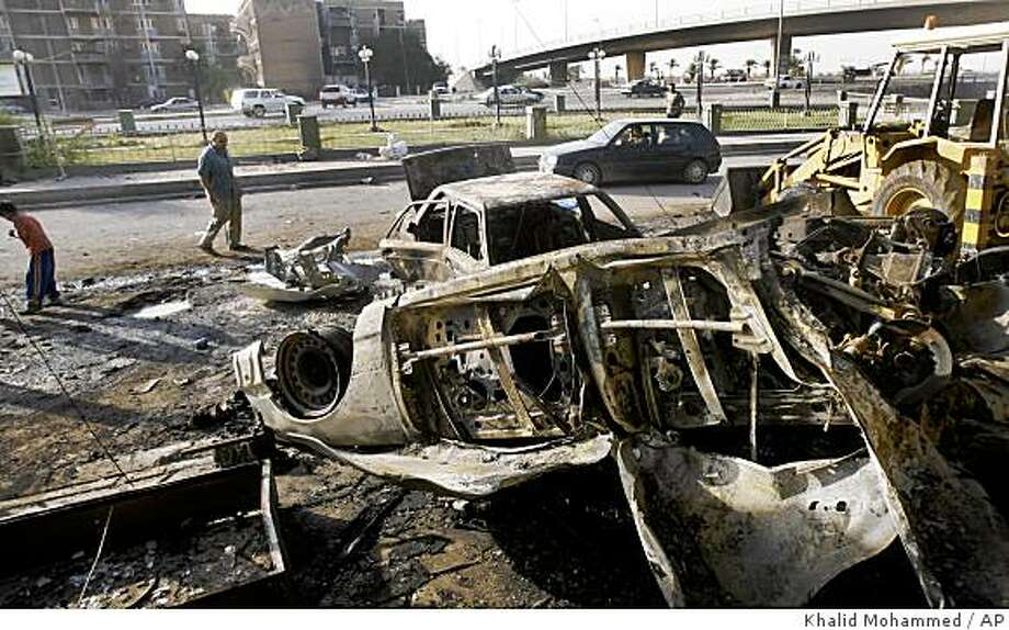 Passers-by observe the scene of a roadside bomb which injured four Iraqi policemen in Maysalon square, Baghdad, Iraq, Saturday, Aug. 9, 2008. (AP Photo/Khalid Mohammed) Photo: Khalid Mohammed, AP