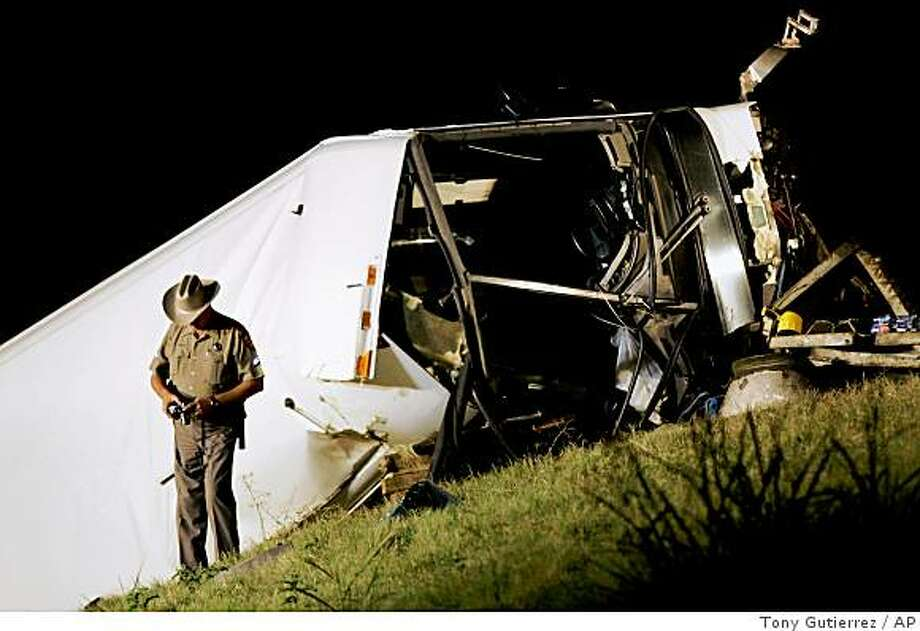 A Texas state trooper makes photographs at a bus accident scene on U.S. 75 North bound that killed at least 12 people early,  Friday, Aug. 8, 2008, in Sherman, Texas. The charter bus ran off the highway overpass north of Dallas and crashed onto its side on a roadway below, killing 12 people early Friday, authorities said.  (AP Photo/Tony Gutierrez) Photo: Tony Gutierrez, AP