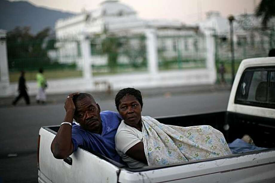 A couple looks on shortly after waking up after sleeping in the back of their truck in front of the collapsed National Palace in Port-au-Prince, Saturday, Feb. 6, 2010. A 7.0-magnitude earthquake hit Haiti on Jan. 12, killing and injuring thousands, but also leaving more than a half million people living in outdoor makeshift camps. Photo: Rodrigo Abd, AP
