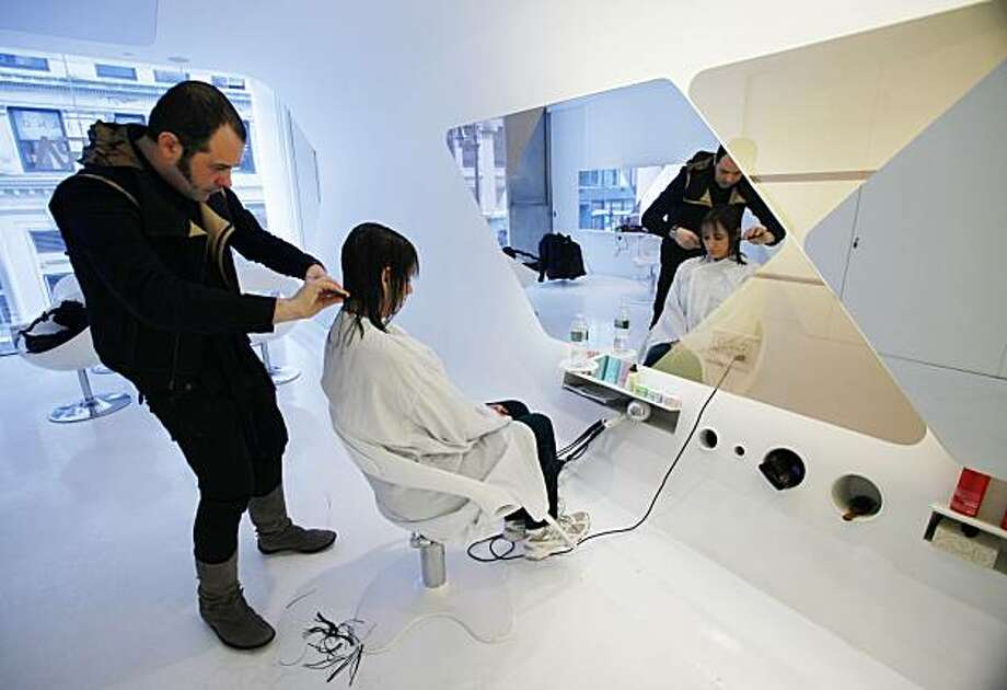 In this photo made Dec. 22, 2009, Diane Linehan of Bayonne, N.J., watches in the mirror as salon owner Cristiano Cora cuts her hair at his spa and salon in New York. The economy's service sector grew slightly in January, while the pace of job losses slowed, signaling a recovery still struggling to gain strength. Photo: Kathy Willens, AP