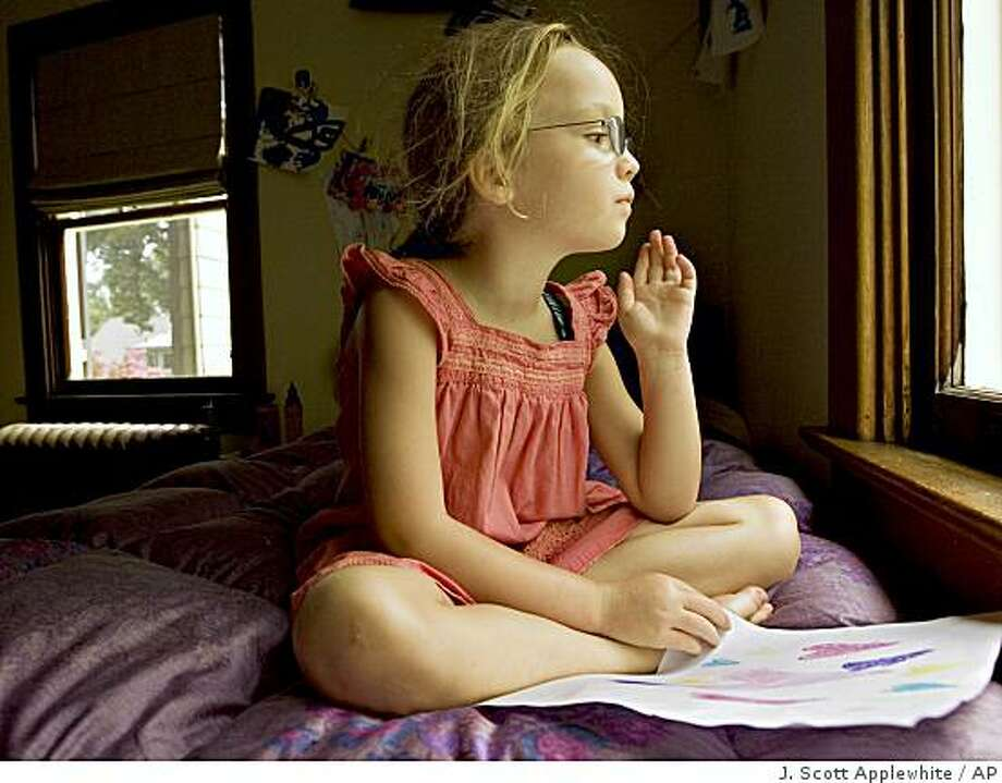 ** ADVANCE FOR SUNDAY, AUG. 10 AND THEREAFTER ** Olivia, five year old daughter of Associated Press writer Nancy Zuckerbrod, gazes out of her bedroom window after drawing with crayons at home in Washington, Tuesday, July 22, 2008. When she enters school in London later this year, Olivia may find that her American pre-school education is short of British standards. (AP Photo/J. Scott Applewhite) Photo: J. Scott Applewhite, AP