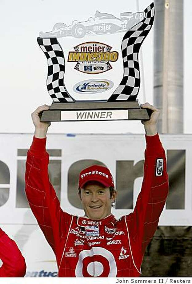Scott Dixon of New Zealand lifts up the trophy as he celebrates winning the Meijer Indy 300 at the Kentucky Speedway in Sparta, Kentucky, August 9, 2008.        REUTERS/John Sommers II      (UNITED STATES) Photo: John Sommers II, Reuters