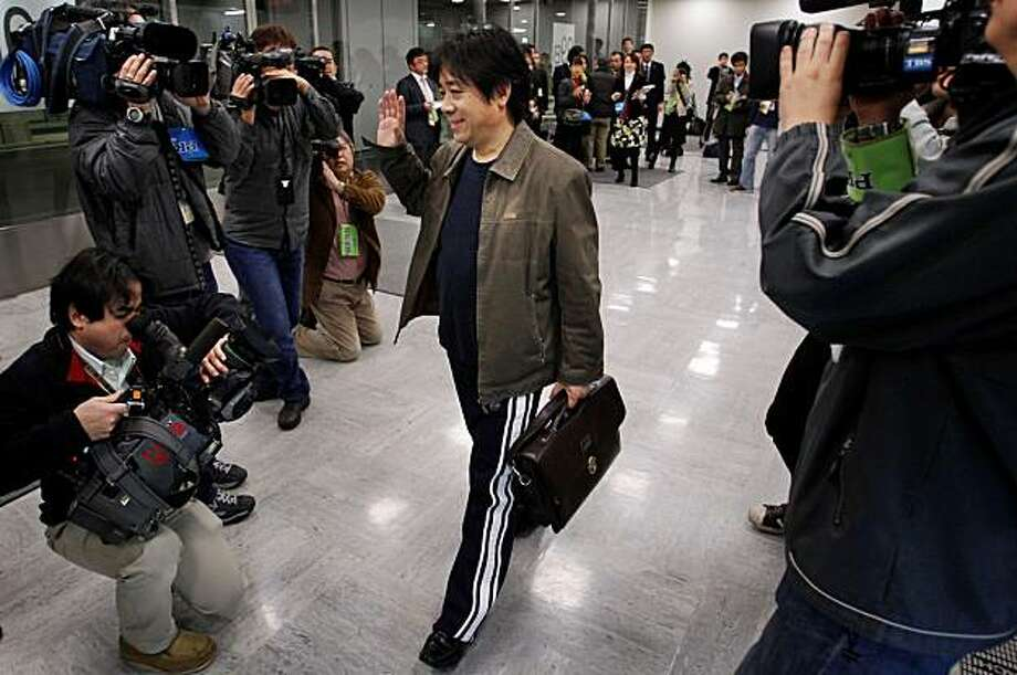 Chinese activist Feng Zhenghu waves at the media after speaking at a news conference at Narita International Airport in Narita, east of Tokyo, Japan, Tuesday, Feb. 2, 2010. Feng, who had camped out at the airport for more than 90 days to protest China's repeated refusal to let him return to his homeland from Japan, announced Tuesday that he is ending his protest after Chinese embassy officials promised to let him return home. Photo: Itsuo Inouye, AP