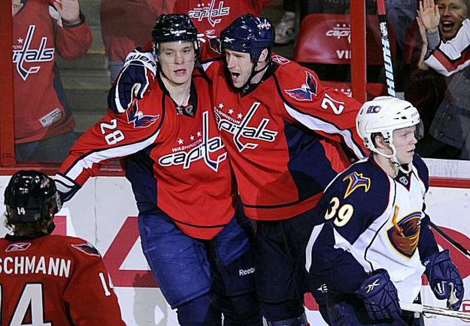 Washington Capitals left wing Alexander Semin (28), of Russia, celebrates his goal with teammate Brooks Laich (21) and Tomas Fleischmann (14) as Atlanta Thrashers defenseman Tobias Enstrom (39), of Sweden, skates by during the third period of an NHL hockey game, Friday, Feb. 5, 2010, in Washington. The Capitals won 5-2. Photo: Nick Wass, AP