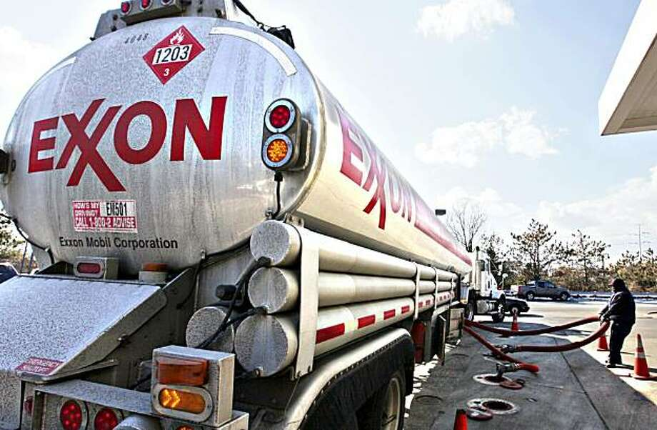 FILE - In this Jan. 30, 2009 file photo, an Exxon tanker truck operated by Corey Moorer, right, of Clinton, Md., makes a refueling stop at an Exxon station in Arlington, Va. Exxon Mobil said Monday, Feb. 1, 2010, its fourth-quarter earnings tumbled 23 percent as higher oil prices squeezed profit margins in its refining business. Photo: J. Scott Applewhite, AP