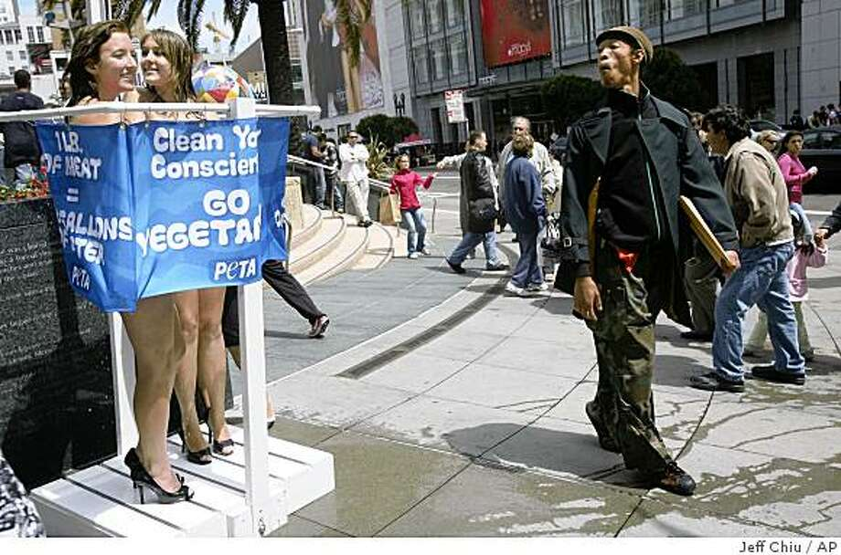 A man walks past Colleen Higgins, left, and Cassandra Callaghan, as they stand in a makeshift shower during a People for the Ethical Treatment of Animals (PETA) protest in San Francisco, Tuesday, Aug. 5, 2008.  (AP Photo/Jeff Chiu) Photo: Jeff Chiu, AP