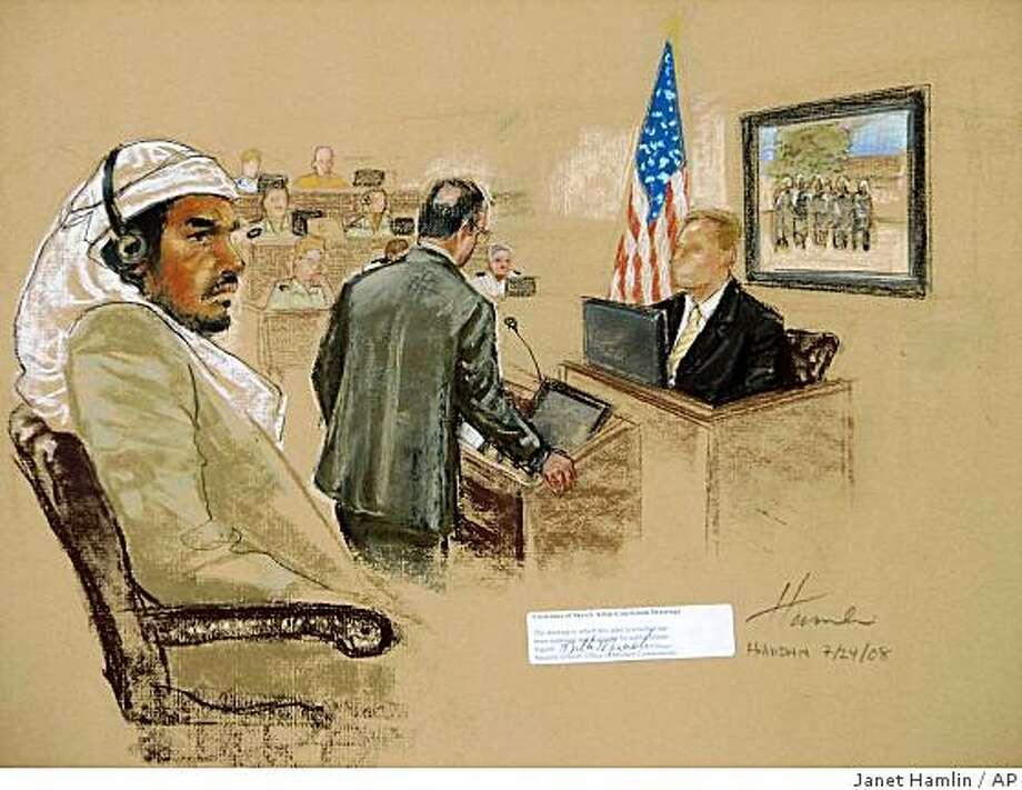 ** FILE ** In this Thursday, July 24, 2008 file photograph of a sketch by courtroom artist Janet Hamlin, reviewed  by the U.S. Military, defendant Salim Ahmed Hamdan, left, watches as FBI agent Craig Donnachie testifies about his interrogations of Hamdan, while a picture of disguised U.S. agents is displayed on a screen, during Hamdan's trial inside the war crimes courthouse at Guantanamo Bay U.S. Naval Base, in Cuba. A jury of six military officers reached a split verdict on Wednesday, Aug. 6, 2008, in the war crimes trial of Salim Ahmed Hamdan, clearing him of some charges but convicting him of others that could send him to prison for life. The judge scheduled a sentencing hearing for later Wednesday.(AP Photo/Janet Hamlin, Pool) Photo: Janet Hamlin, AP