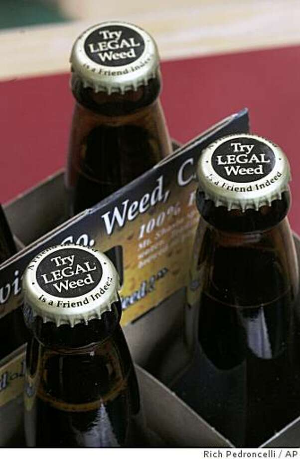 """Bottles of  Mt. Shasta Brewing Co. beer, with the  logo """"Try Legal Weed"""" on the caps are seen in a market in Sacramento, Calif., Wednesday,  April 23, 2008.  Vaune Dillmann, owner of the brewery in Weed, Calif., is in a dispute with the Alcohol and Tobacco Tax and Trade Bureau over the caps.  The agency says  the wording could """" mislead consumers about the characteristics of the alcoholic beverage"""".   Dillmann said he doesn't advocate marijuana use, it's just a play on the name of the town where he brews his beer. (AP Photo/Rich Pedroncelli) Photo: Rich Pedroncelli, AP"""