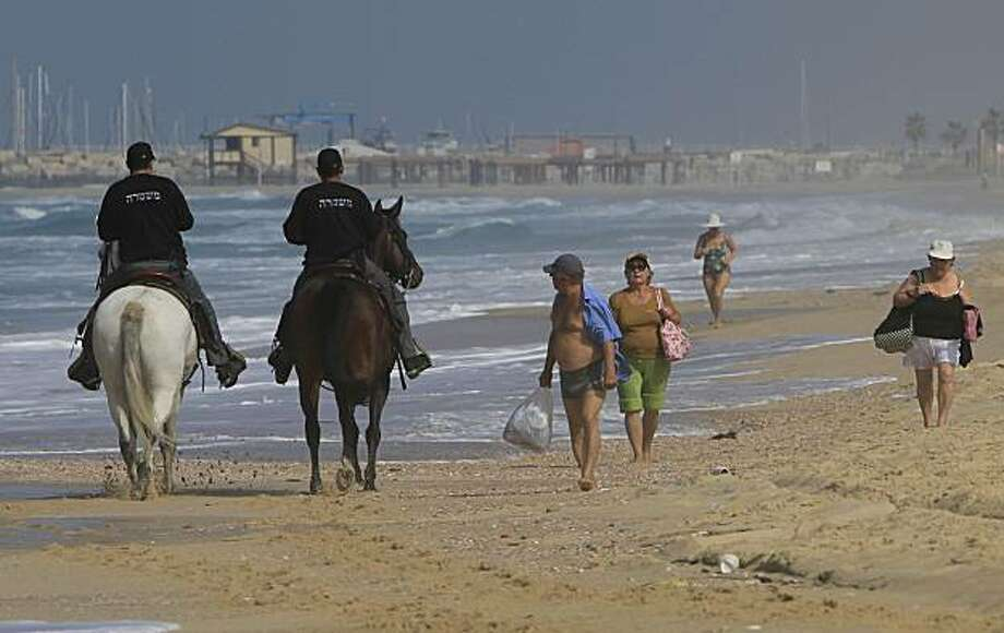 Israeli policemen, riding on horses, patrol along the beach in the southern Israeli town of Ashkelon, near the Gaza border, Tuesday, Feb. 2, 2010. On Monday, at least two barrels full of explosives washed up on Israeli beaches north of Gaza. Israeli mediaspeculated that Hamas was trying to avenge the Hamas commander killing in Dubai, but police would not confirm that. Police safely disposed of the explosives. Photo: Tsafrir Abayov, AP