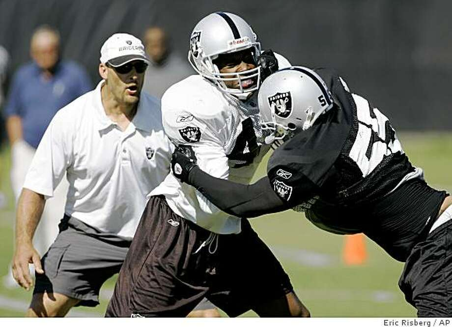 Oakland Raiders linebacker Robert Thomas, tries to tackle running back Louis Rankin, center, during their football training camp in Napa, Calif., Thursday, July 31, 2008. Associated Press photo by Eric Risberg Photo: Eric Risberg, AP