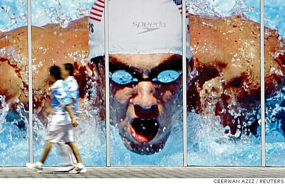 Olympic volunteers walk past a giant poster of U.S. swimmer Michael Phelps near the National Aquatics Center Olympic swimming venue in Beijing August 2, 2008.     REUTERS/Ceerwan Aziz (CHINA) Photo: CEERWAN AZIZ, REUTERS