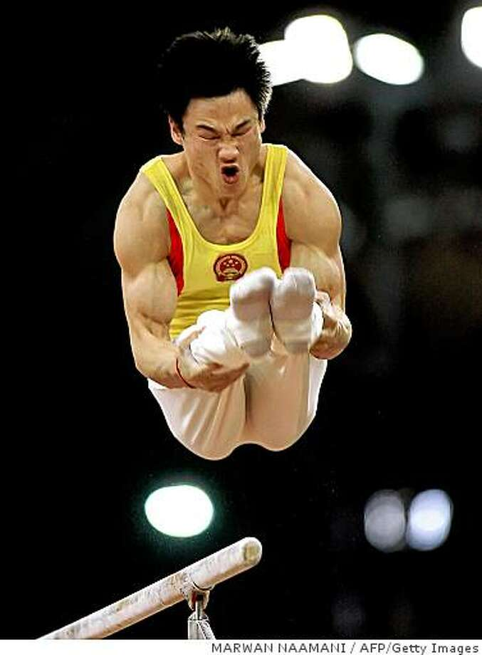 FILES TO GO WITH AFP STORIES OLY-JO-2008(FILES) A picture taken on December 4, 2006 shows Chinese Gymnast Yang Wei performing his routine on parallel bars in the men Artistic Gymnastics Individual All-Round final at Aspire center in the 15th Asian Games in Doha. The Olympic Games 2008 will be held in Beijing from August 8 to August 24.   AFP PHOTO/ MARWAN NAAMANI (Photo credit should read MARWAN NAAMANI/AFP/Getty Images) Photo: MARWAN NAAMANI, AFP/Getty Images