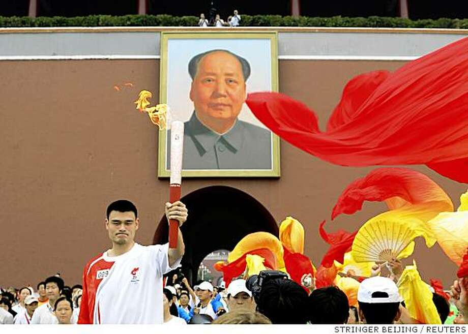 Torchbearer Yao Ming holds the torch as he runs through the Tiananmen Gate during the 2008 Beijing Olympics torch relay in Beijing August 6, 2008.  REUTERS/Cao Taeg  (CHINA) Photo: STRINGER BEIJING, REUTERS