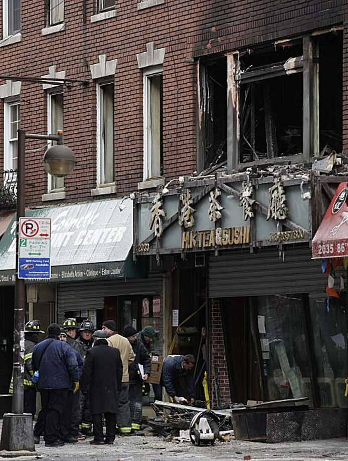 New York City fire marshals look through debris while investigating a fatal fire in Brooklyn early in the morning Saturday, Jan. 30, 2010, New York. The fire engulfed a three-story building on a busy commercial strip injuring several firefighters during the hours it took to get the blaze under control. Photo: Julie Jacobson, AP