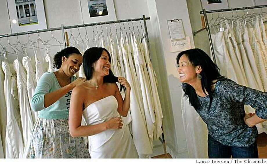 Suzanne Tran center, gets help from Chasa Toliver assistant showroom manager at Amy Kuschel Bride in San Francisco and her friend Emmy Ma who is also in for her fitting, Wednesday August 6, 2008. Tran along with thousands of others nation wide will be married or celebrate a special event on Friday 8/8/08. These numbers are considered so lucky that weddings have been scheduled in advance for moths if not years.Photographed in San Francisco Wednesday August 6, 2008. Photo: Lance Iversen, The Chronicle