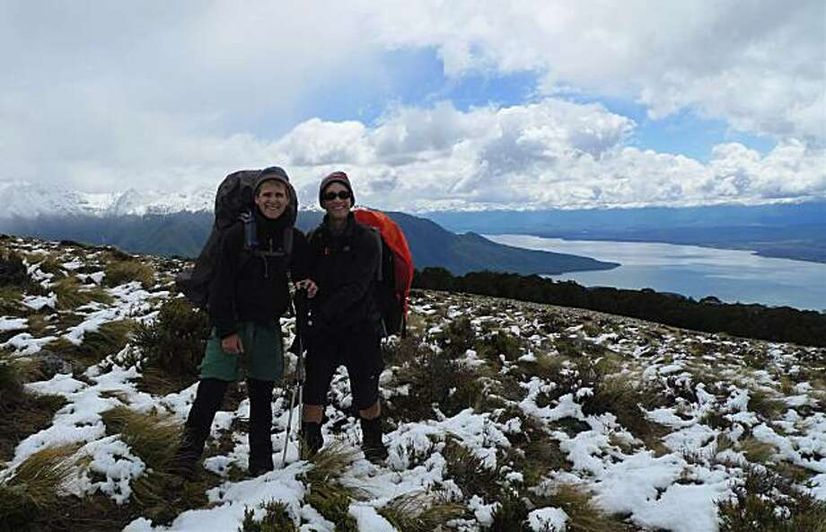 Mara Hancock (left) and Tracy Davis (right) enjoy snow in summer in Fjordlands National Park, New Zealand; Lake Te Anou and Southern Alps in the background. Photo: Courtesy, Mara Hancock And Tracy Davis