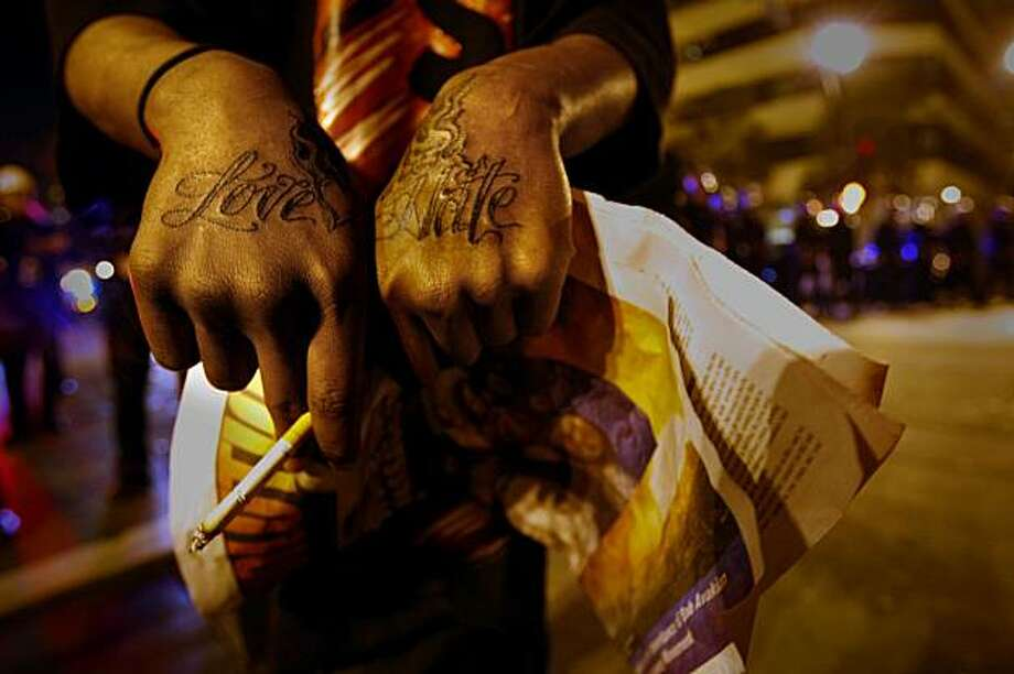 A young Oakland resident shows his views of his hometown that was tatooed on his hands as the police circled the  protesters as they started rioting through the streets in downtown Oakland, Wed. Jan 7, 2009, in Oakland, Calif. Photo: Lacy Atkins, The Chronicle