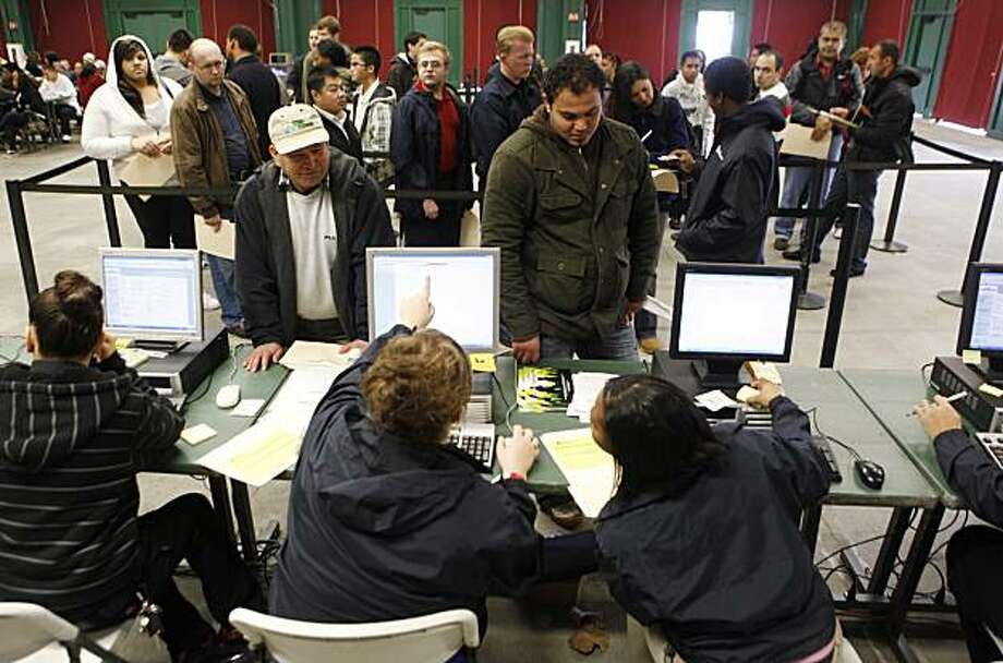In this Sunday, Jan. 23, 2010 photo, Job applicants, upper, talk with job recruiters at a job fair in Santa Clara, Calif. The number of new claims for unemployment benefits fell less than expected last week, fresh evidence the job market remains a weak spot in the economic recovery. Photo: Paul Sakuma, AP