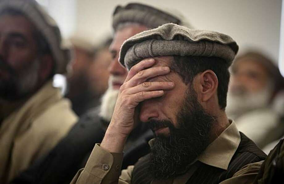 A Shinwari tribal leader holds his head as he listens to a speaker, unseen, during a gathering of Shinwari tribal leaders at the Afghan Border Police compound in Jalalabad, Nangarhar province east of Kabul, Afghanistan, Wednesday, Jan. 27, 2010. An eastern Afghan tribe has signed a pact to keep the Taliban out of their lands _ pledging to burn down the houses of those who shelter insurgents and force them to pay fines high as $20,000. Photo: Altaf Qadri, AP