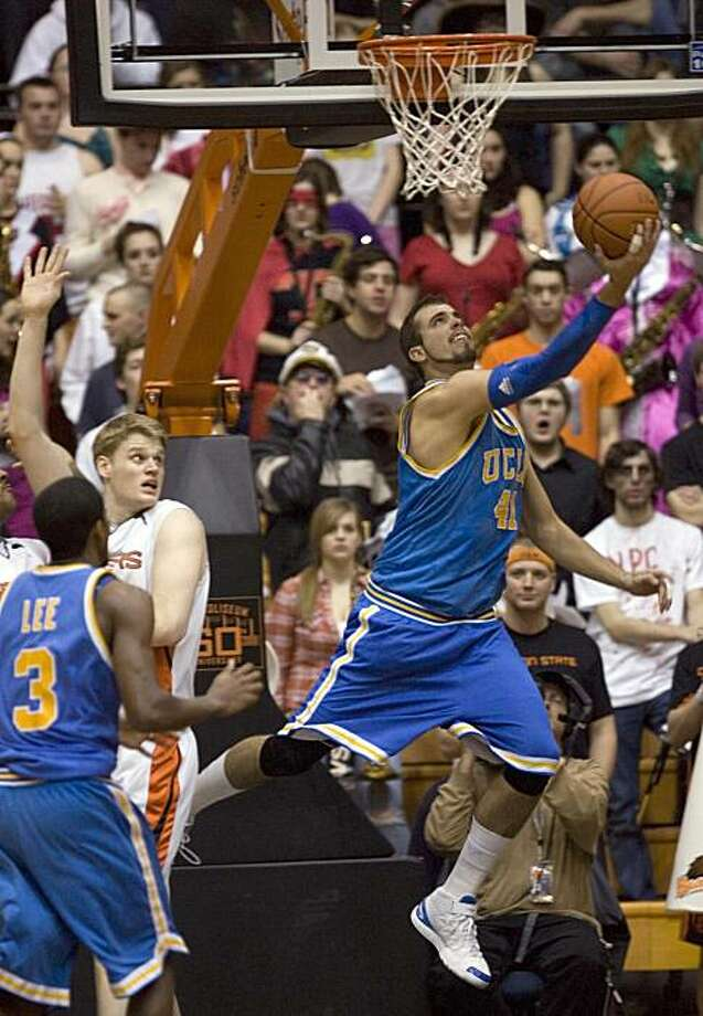 Kikola Dragovic, right, goes in for a reverse layup past Oregon State center Roeland Schaftenaar and teammate Malcolm Lee, left, during the second half of their NCAA college basketball game in Corvallis, Ore., Saturday, Jan. 30,  2010.  Dragovic scored 13points as they beat Oregon State 62-52. Photo: Don Ryan, AP