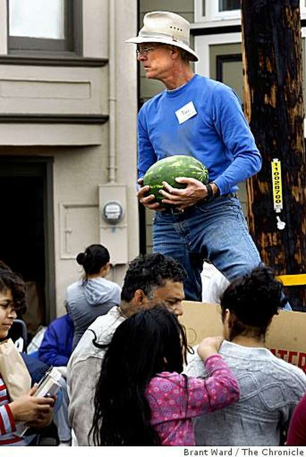 Hal Meier makes sure everyone leaves with a ripe melon. Nina Pickerrell, a Deacon at Grace Cathedral in San Francisco, Calif. gives away bags of groceries to her Bayview neighbors every week, this give away on Monday, July 28, 2008.  Photo by Brant Ward / The Chronicle Photo: Brant Ward, The Chronicle