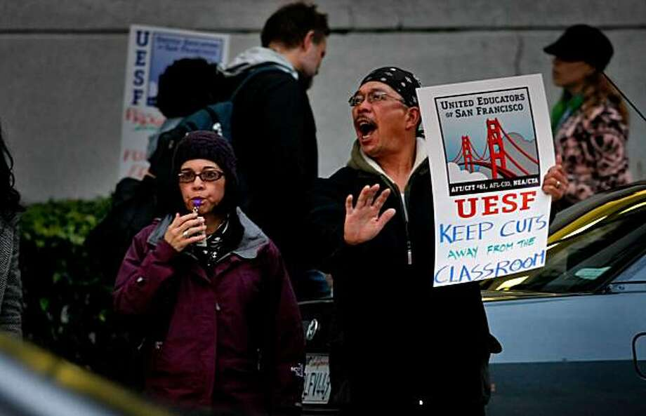 Jean Parker Elementary teacher Celia Magtoto and her husband, Felix, signal to traffic to honk in protest of school budget cuts Tuesday in San Francisco. Photo: Lacy Atkins, The Chronicle