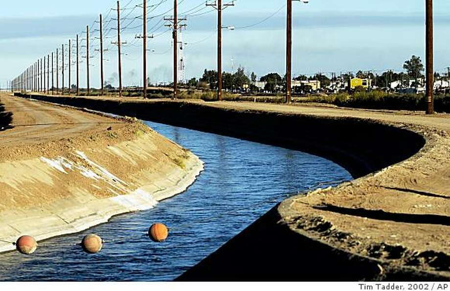 ** FILE ** In this Dec. 30, 2002, file photo, the All-American Canal runs along the United States border with Mexico near Calexico, Calif. When crews finish lining the All-American Canal with concrete, the waterway will be deeper, faster and more dangerous for migrants crossing the border illegally from Mexico.  (AP Photo/Tim Tadder, file) Photo: Tim Tadder, 2002, AP