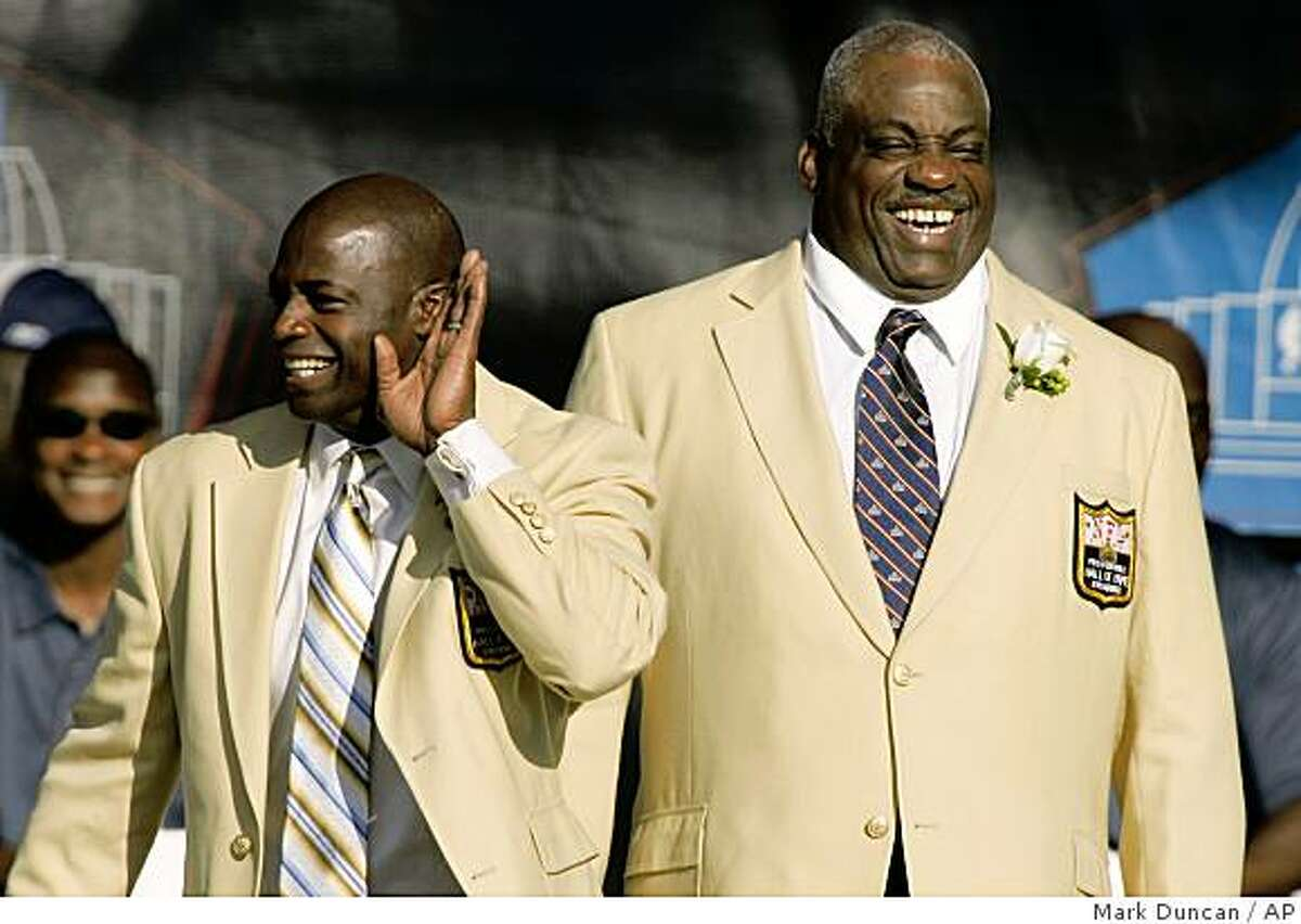 Former Washington Redskins' Darrell Green, left, jokes around as fans cheer for him at the Pro Football Hall of Fame on Saturday, Aug. 2, 2008, in Canton, Ohio. At right is former San Diego and San Francisco defensive end Fred Dean. (AP Photo/Mark Duncan)