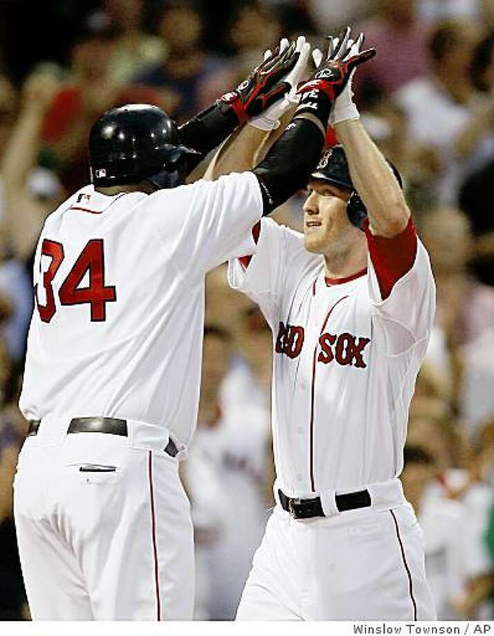 Boston Red Sox's Jason Bay is greeted at home plate by David Ortiz (34) after Bay's three-run home run against the Oakland Athletics during the first inning of a baseball game at Fenway Park in Boston on Saturday, Aug. 2, 2008. Photo: Winslow Townson, AP