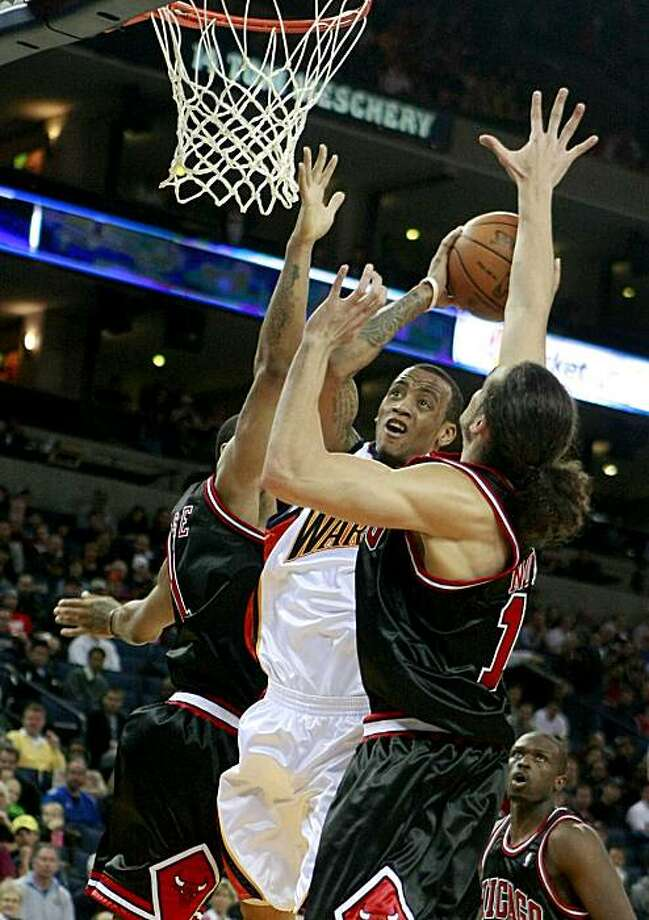 The Warriors' Monta Ellis goes up for a basket while being defended by the Bulls' Joakim Noah in Oakland on Monday. Photo: Brant Ward, The Chronicle