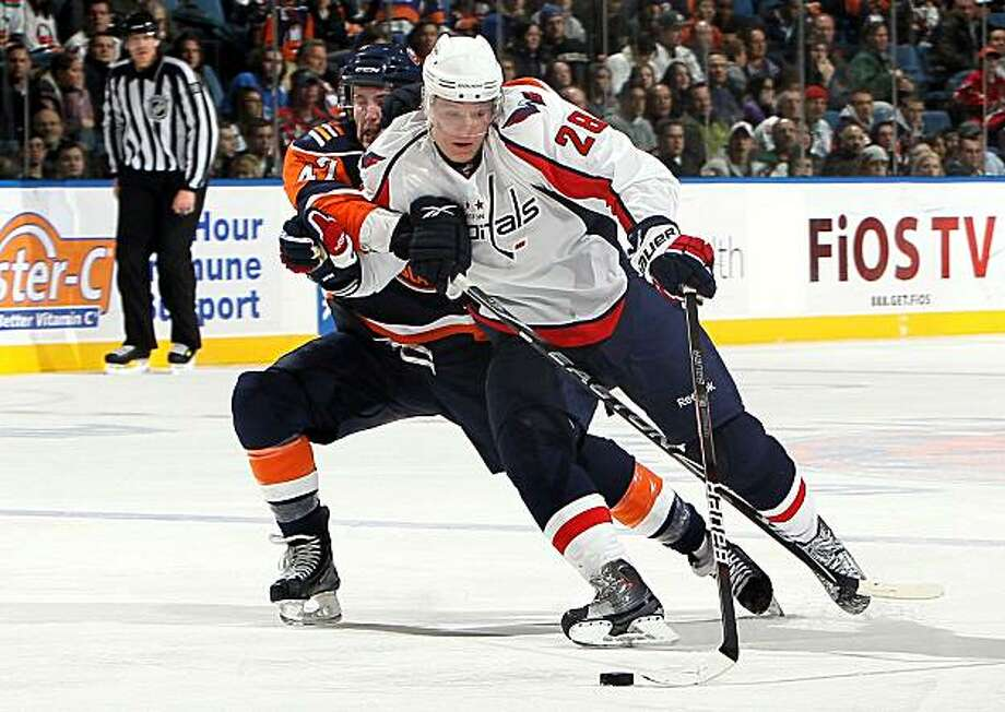 UNIONDALE, NY - JANUARY 26:  Andrew MacDonald #47 of the New York Islanders commits a holding penalty against Alexander Semin #28 of the Washington Capitals in the third period on January 26, 2010 at Nassau Coliseum in Uniondale, New York. Photo: Jim McIsaac, Getty Images