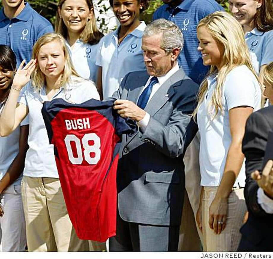 U.S. President George W. Bush holds up a softball jersey presented to him by U.S. Olympic softball player Jennie Finch (R) at a photo opportunity with U.S. Olympic athletes bound for Beijing in the Rose Garden of the White House in Washington, July 21, 2008.      REUTERS/Jason Reed      (UNITED STATES) Photo: JASON REED, Reuters