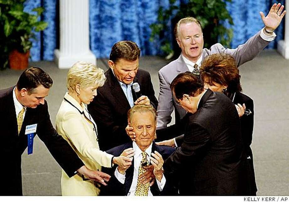 ** FILE ** In this June 18, 2003 file photo, TV evangelists, from left: Billy Joe Daugherty; Gloria Copeland; Kenneth Copeland; Charles Green; Richard Roberts; and Lindsay Roberts lay hands on Oral Roberts, 85,  during the International Charismatic Bible Ministries conference in the Mabee Center at Oral Roberts University in Tulsa, Okla. (AP Photo/Tulsa World, Kelly Kerr, file) Photo: KELLY KERR, AP