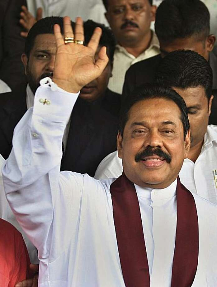 Sri Lankan President Mahinda Rajapaksa waves after hearing the election results in Colombo, Sri Lanka, Wednesday, Jan. 27, 2010.  Rajapaksa won a resounding re-election victory Wednesday, beating back a challenge from his former army chief, who rejected the official results and said he feared arrest as troops surrounded his hotel. Photo: Rafiq Maqbool, AP