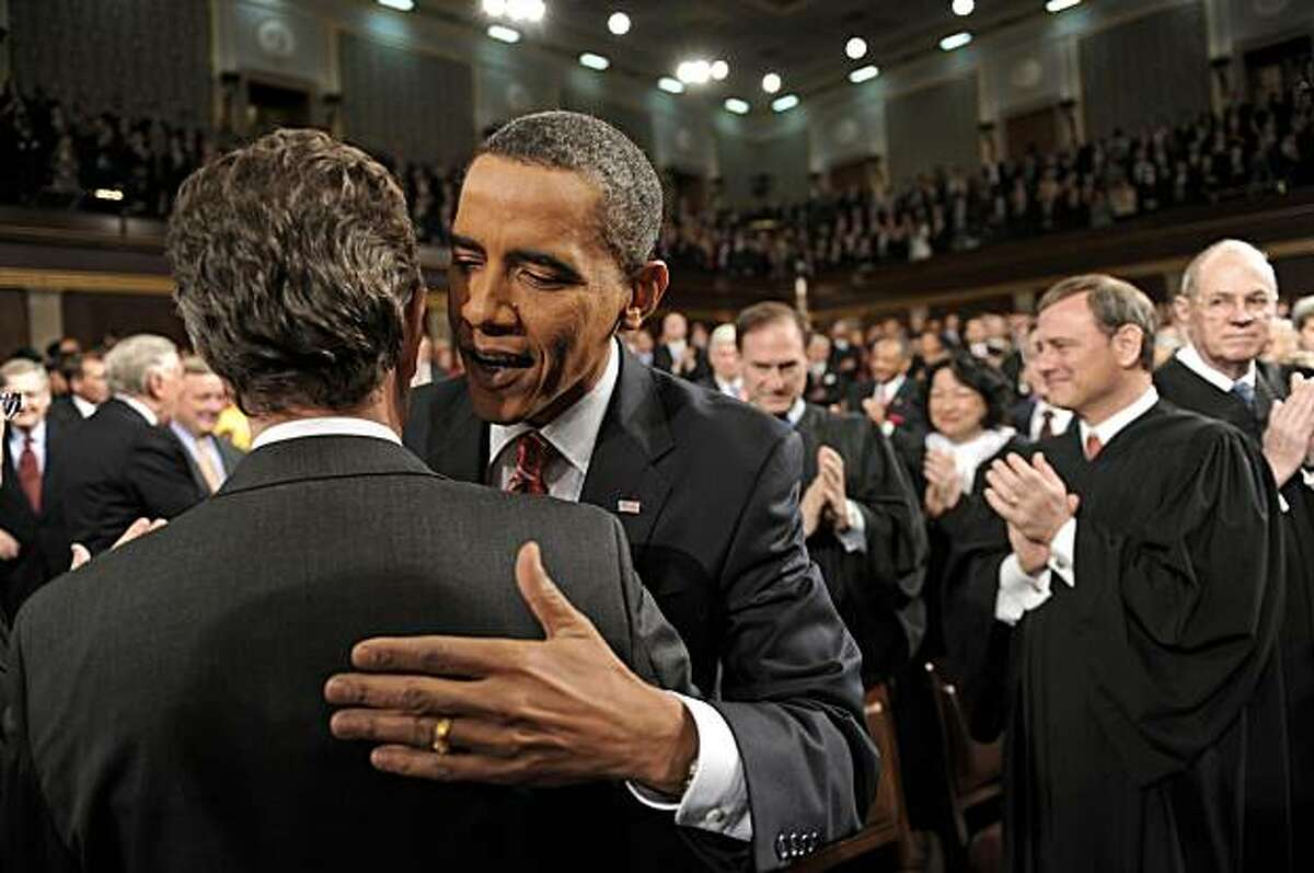 President Barack Obama greets Treasury Secretary Tim Geithner as he walks down the center aisle greeting members of Congress on his way to deliver his State of the Union address on Capitol Hill in Washington, Wednesday, Jan. 27, 2010.