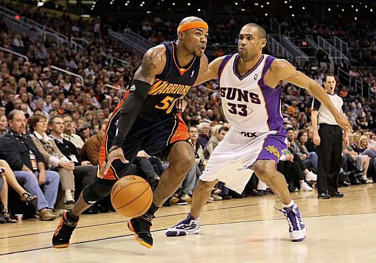 Corey Maggette of the Golden State Warriors drives the ball past Grant Hill of the Phoenix Suns on Saturday in Phoenix.