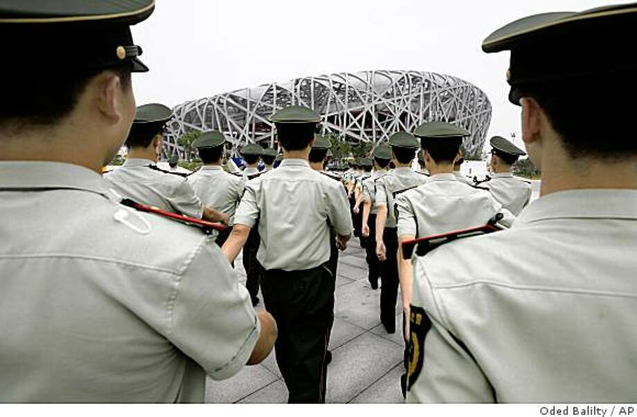 Chinese paramilitary police officers march into the National Stadium,  known as the Bird's Nest, in Beijing, Wednesday, July 30, 2008. The stadium will host the opening and closing ceremonies and athletics competition for the games, which open on Aug. 8. Associated Press photo by Oded Balilty Photo: Oded Balilty, AP