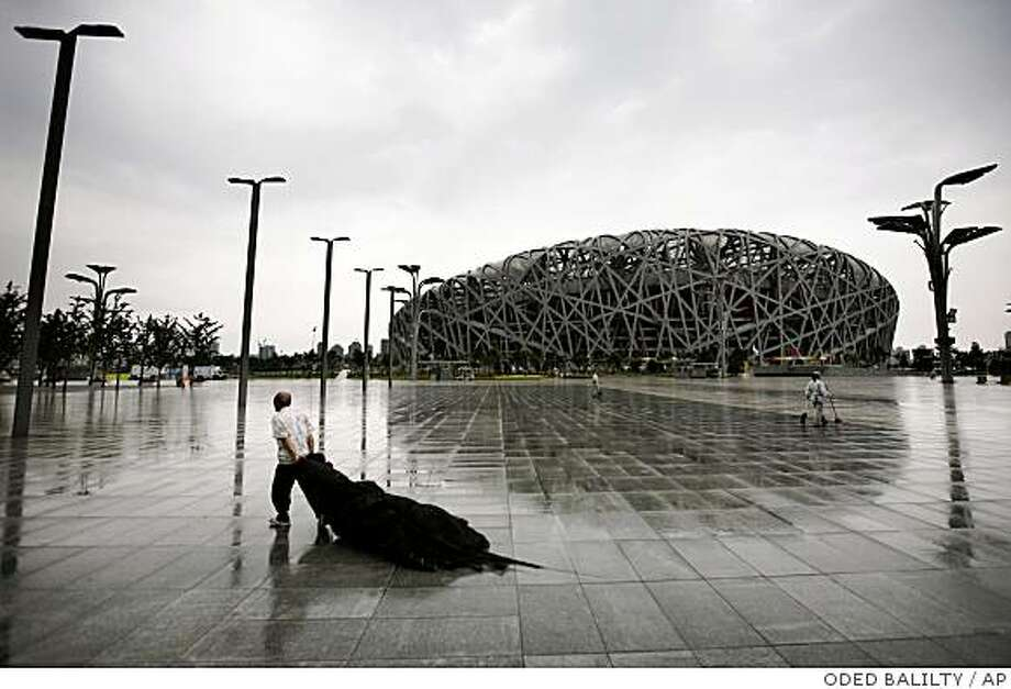 A Chinese worker carries a net at the Olympic green with a backdrop of the National Olympic Stadium in Beijing, Thursday, July 31, 2008. The stadium, known as the Bird's Nest for its elaborate network of steel girders, will host the opening and closing ceremonies and athletics competition for the games, which open on Aug. 8. (AP Photo/Oded Balilty) Photo: ODED BALILTY, AP