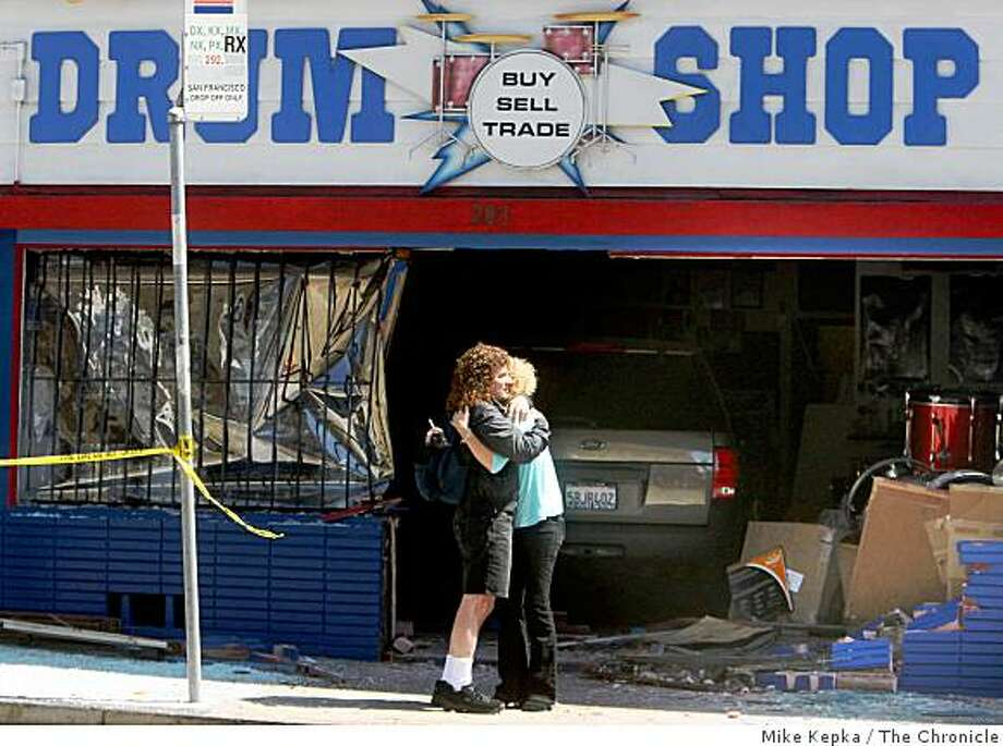 "Sam and Janis Adato embrace In front of their shop, Sam Adato's Drum Shop at 283 9th Street, after a Ford Explorer ran into the front of the shop around 11 a.m. on Thursday July 31, 2008 in San Francisco, Calif. ""Thank God I wasn't in there and no one was hurt,"" said Sam Adato who was running a little late to work because of traffic.Photo by Mike Kepka / The Chronicle Photo: Mike Kepka, The Chronicle"