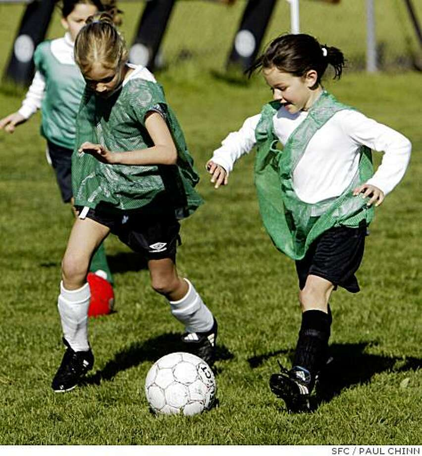 Grace Strausser (L) and Caroline Newman try to impress coaches evaluating their skills at the Lamorinda league tryouts.  Tryouts for youth soccer teams on 3/6/04 in Moraga.PAUL CHINN/The Chronicle Photo: PAUL CHINN, SFC